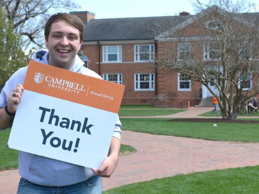 Student Gray Barnhill stands in Academic Circle with thank you sign