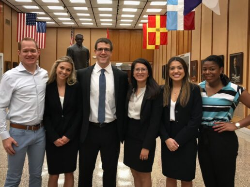 Photo of Professor Dan Tilly standing in lobby of San Juan Puerto Rico Courthouse with four students and Morgan Pierce on the far right