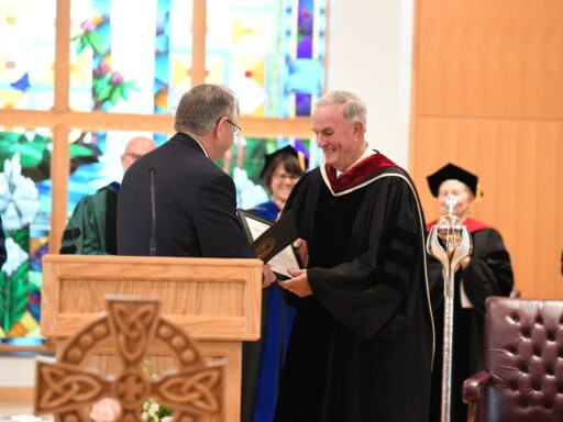 Michael Cogdill of the Divinity school accepts an Order of the Long Leaf Pine award from Senator Jim Burgess