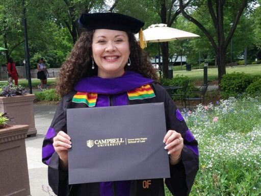 Photo of Joonu-Noel-Coste in her graduation regalia standing outside Duke Energy Center holding a black folder with gold letters that read Campbell University Norman Adrian Wiggins School of Law