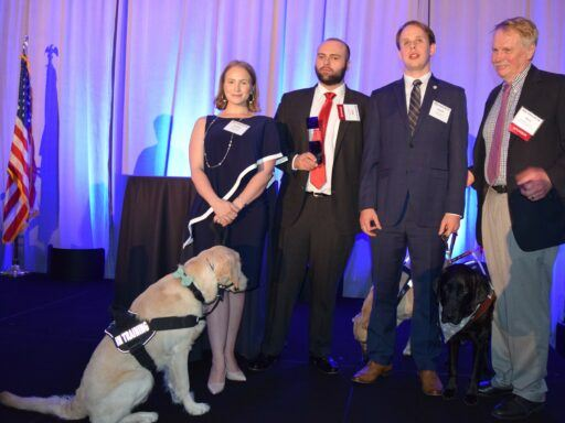 law students with seeing eye dog on stage to accept award