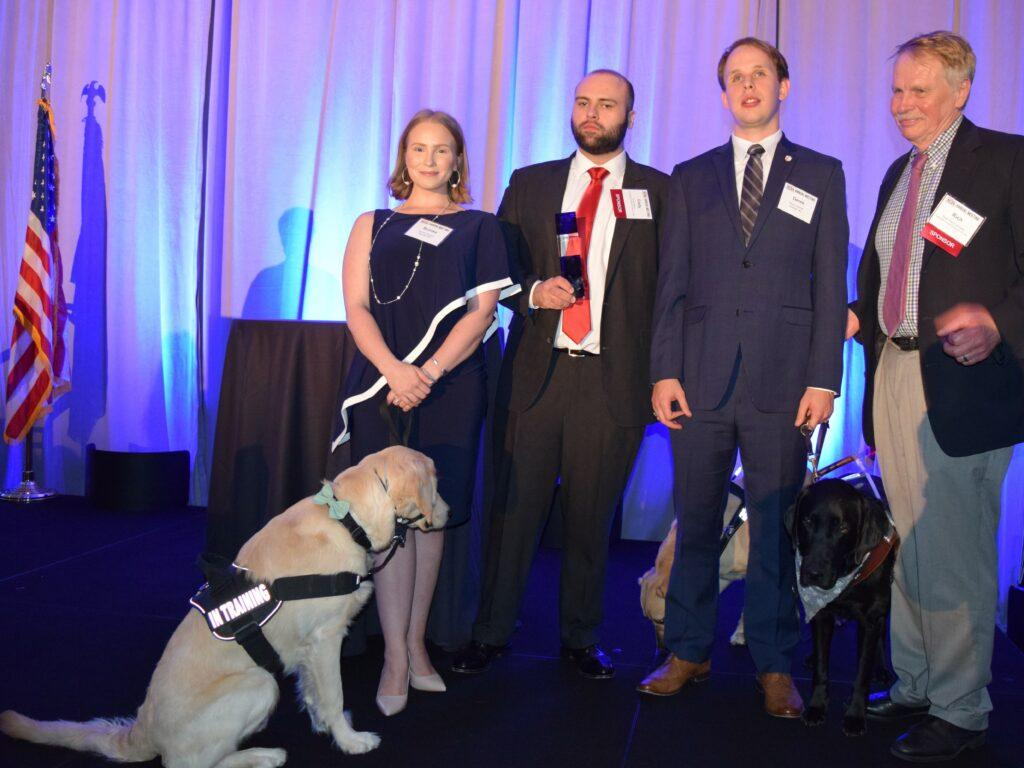 Photo of Brooks Barrett '19, her service dog Bailey, Cody Davis '18, his service dog Clark, Derrick Dittmar '19 and Dean J. Rich Leonard on stage at the annual NCBA Pro Bono Awards posing