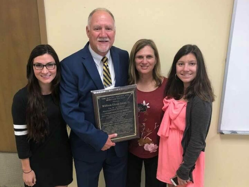Glenn Jonas with wife and two daughters holding plaque received for Carver award