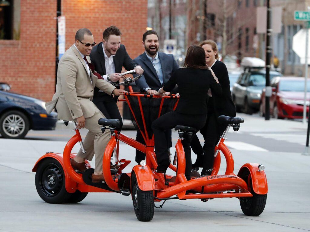 Photo of law students riding the Cobi Conference Bike at Union Station in downtown Raleigh.