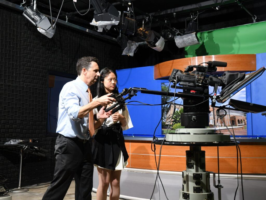 Brian Bowman and a Chinese exchange student at the helm of a camera in the tv studio