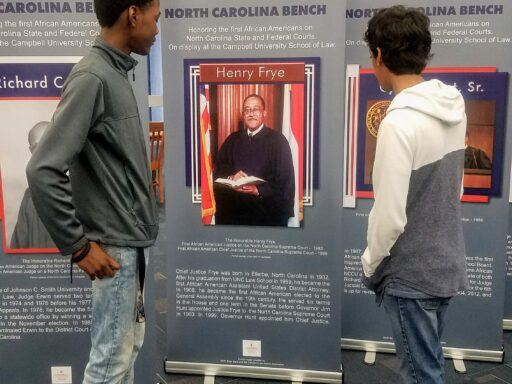 Photo of St. Augustine University students looking at Campbell Law's First African American Judges exhibit banners