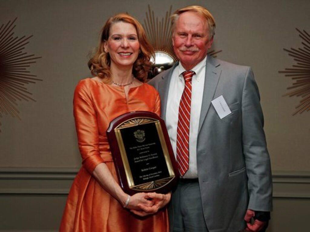 Photo of FLONC Kristin Cooper and Dean J. Rich Leonard holding Everett Award
