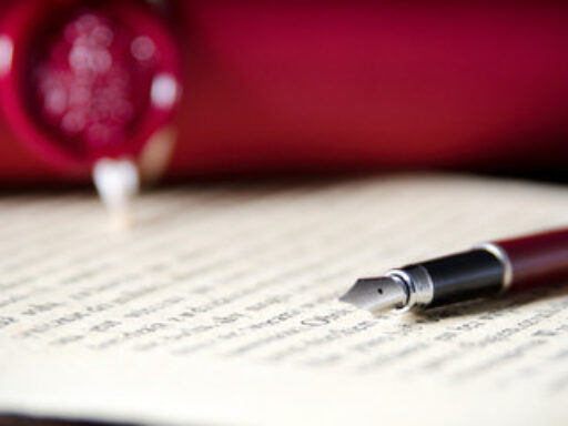 Photo of an official looking legal document with a caligraphy pen