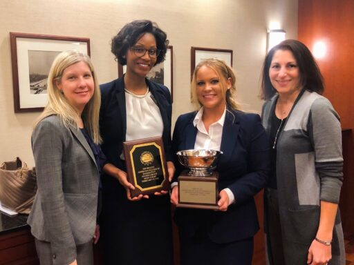 Photo of Campbell Law advocates and coaches posing with hardware after winning regional competition in DC