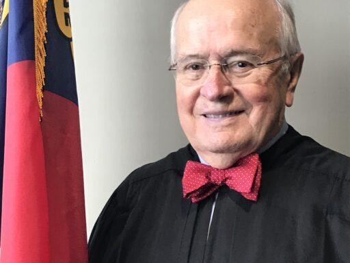Photo of Judge Britt in black robe standing next to NC flag