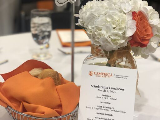 Photo of a table with an orange napkin in a bread basket on white table cloth with orange and white flowers and a sign with a No. 3 on it and a card that says Scholaship luncheon with law school logo
