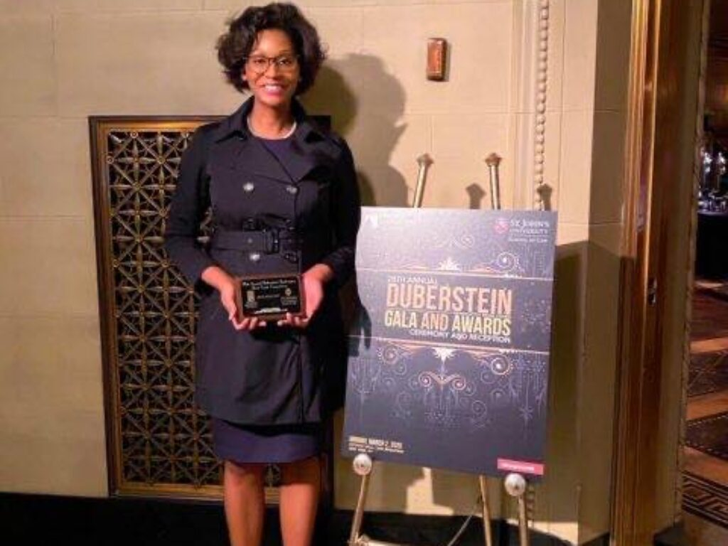 Photo of Destiney Parker '20 holding Duberstein Best Advocate award in front of Gala sign in New York City