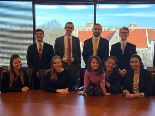 Photo of 17th Willem Vis Campbell Law advocates pose in Dean's Conference room with coach Professor Raluca Papadima