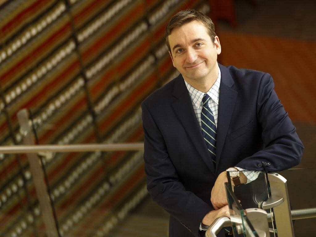 Photo of Professor Anthony Ghiotto posing in the law school library on the stairs with books behind him