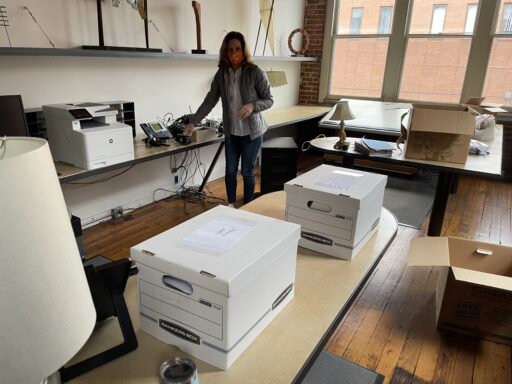 Photo of Blanchard Community Law Clinic Director Ashley Campbell standing amid unpacked boxes in new clinic space