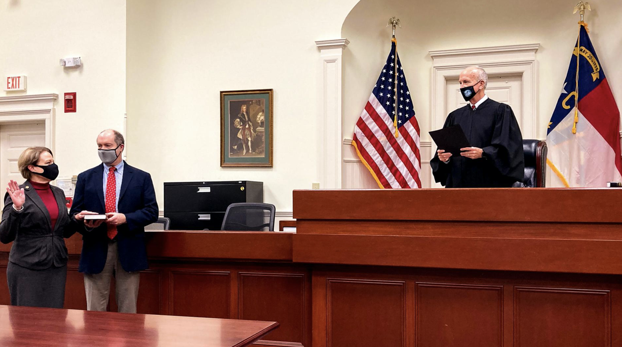 Photo of Chief Judge Donna Stroud (left) stands with her husband, J. Wilson Stroud, while Chief Justice Paul Newby administers her oath of office.