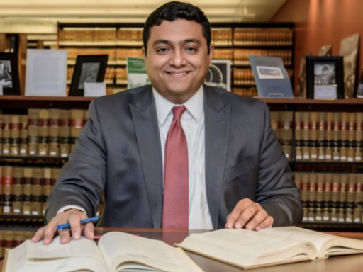 Photo of Rashad Hauter '11 sitting in library a table with a large book open in front of him