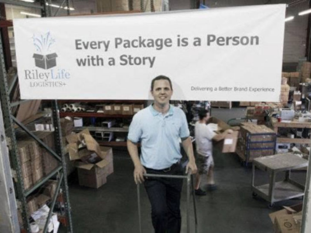 Chris Bingham with a banner of his shipping company