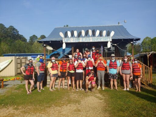 group of students in athletic wear stand for group photo in front of kayaking facility