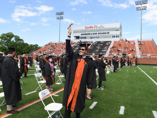 Graduate raises diploma in front row of Barker Lane socially distanced field seating