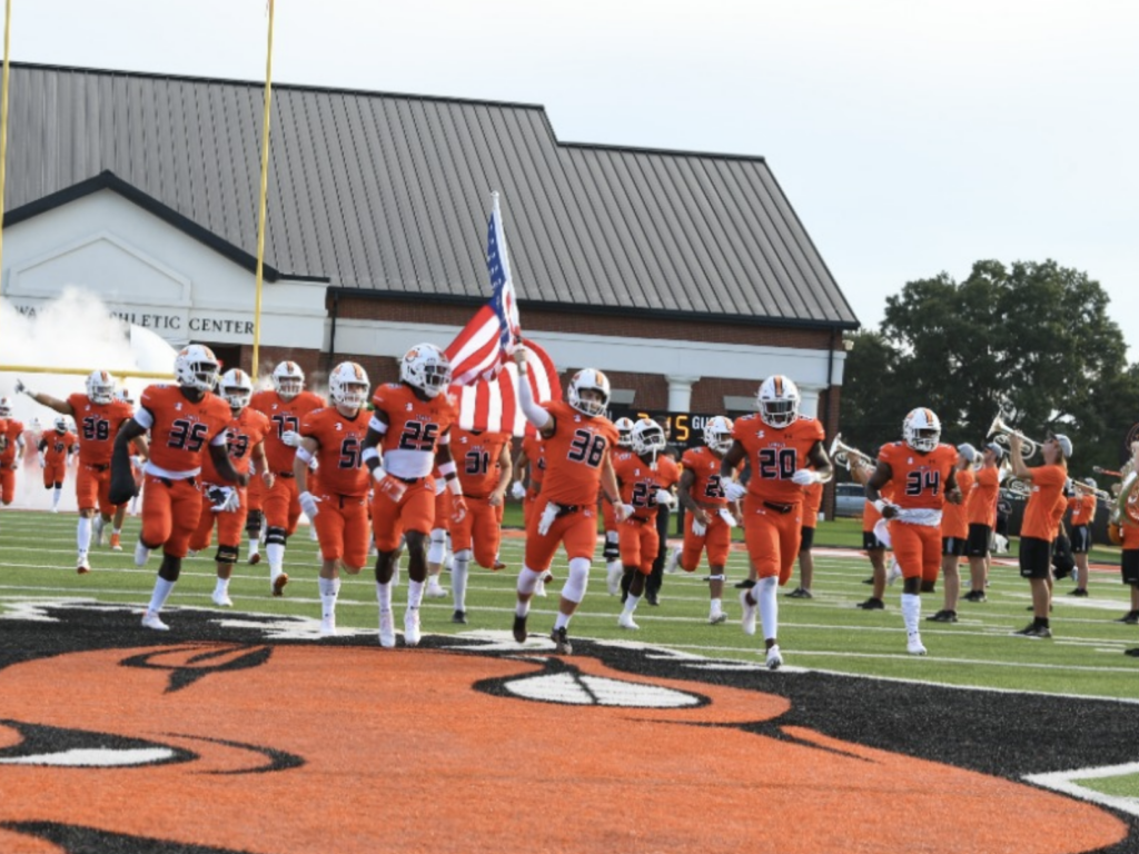 Picture of Campbell University Football Team hitting the field during a game opener with white smoke billowing out behind them