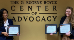 Photo of Old Kivett winners Tia Overway and Wallace Driggers in front of Gene Boyce Advocacy Center