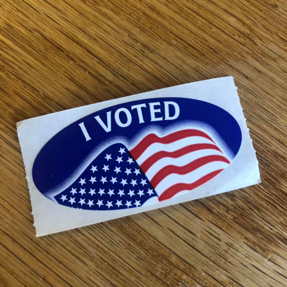 Photo of blue sticker with the words I Voted in white letters above the American flag