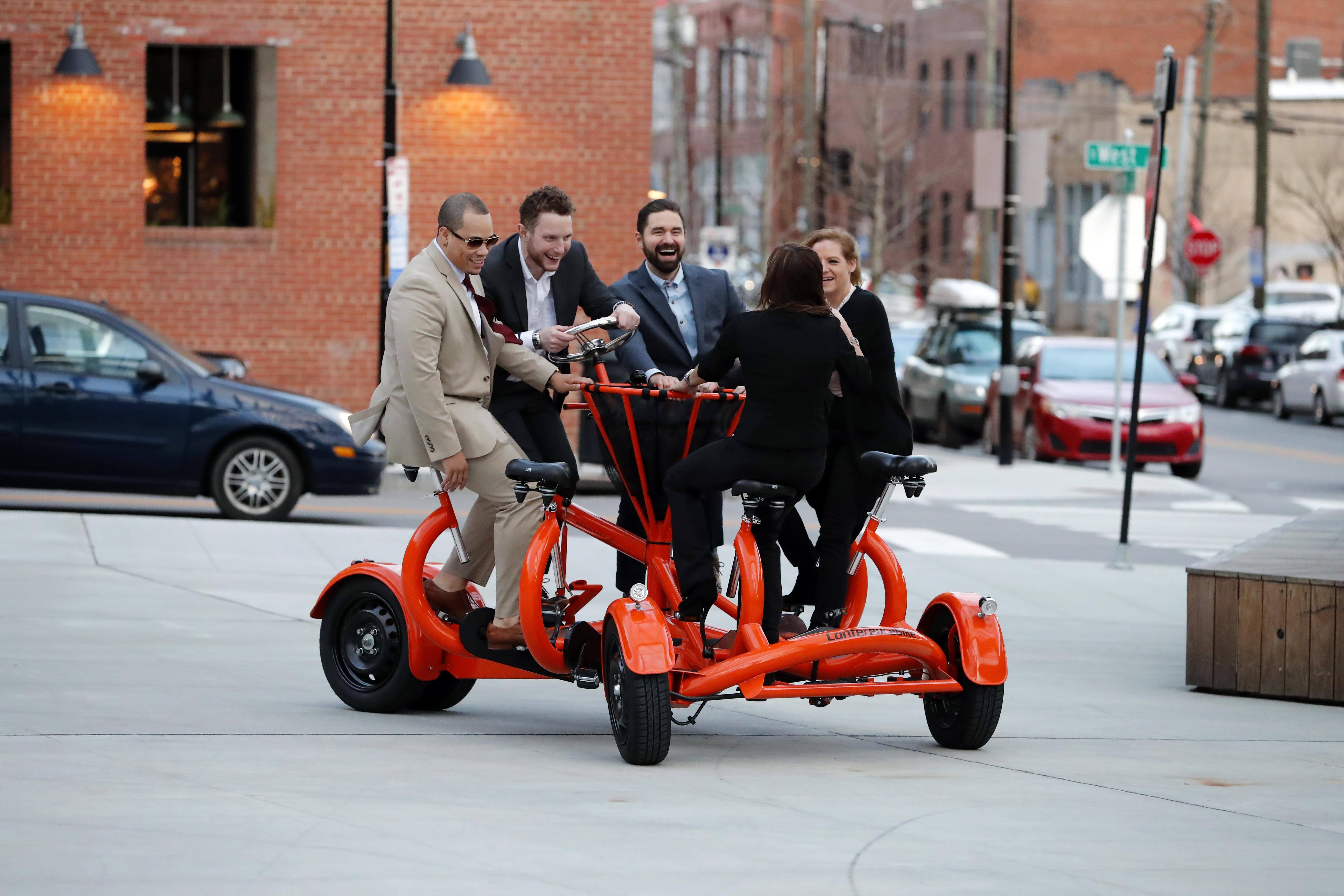 Photo of law students riding an orange conference bike