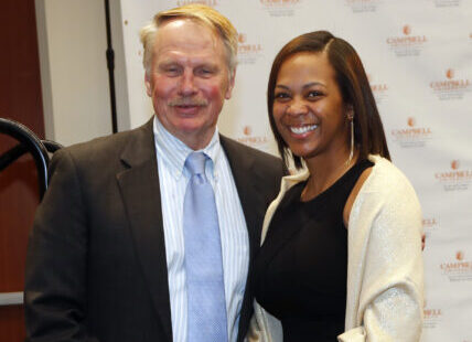 Photo of Dean Leonard posing with an award winner at Family Day Law Banquet