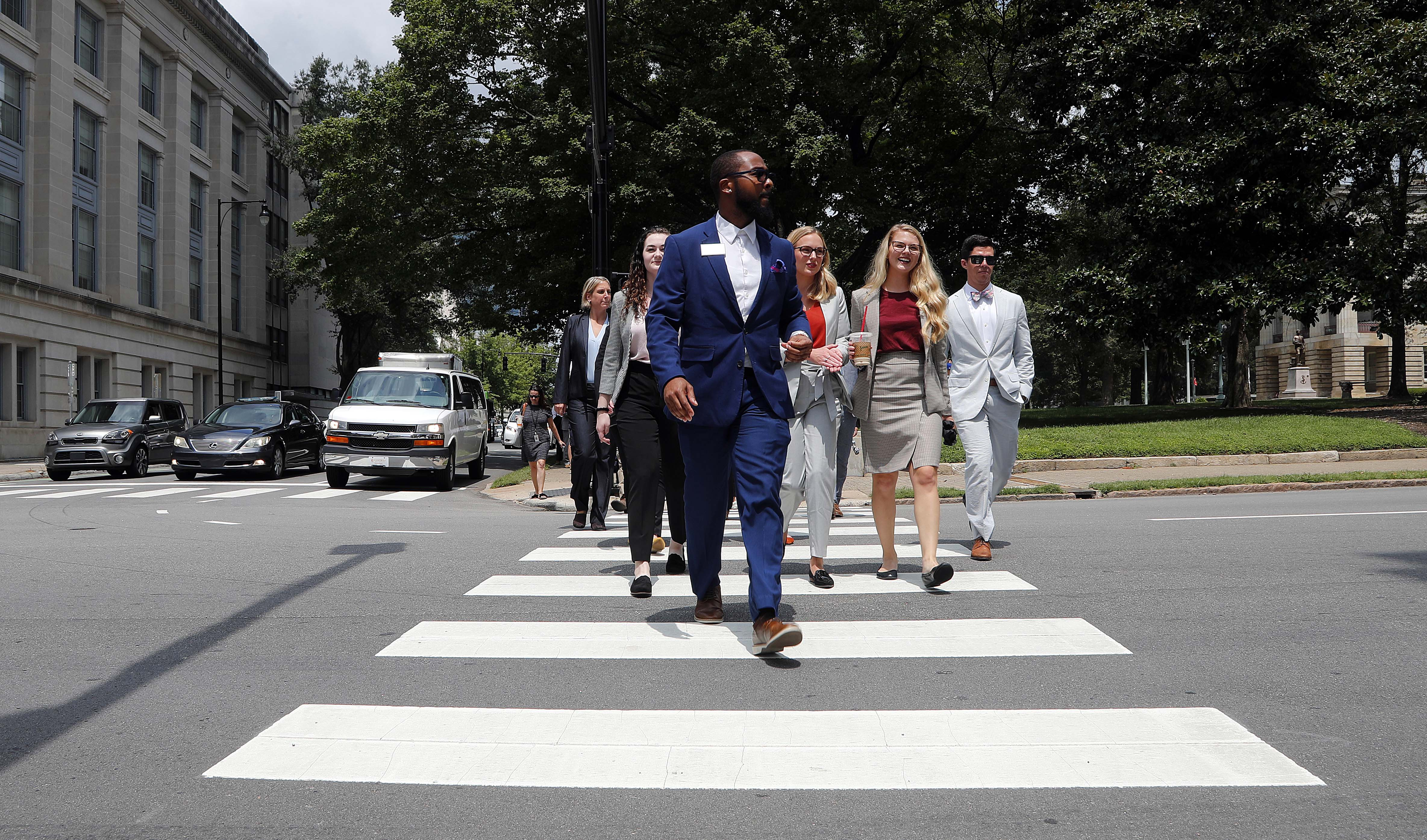 Photo of law students walking across a street on a crosswalk during the Dean's Court Crawl during orientation