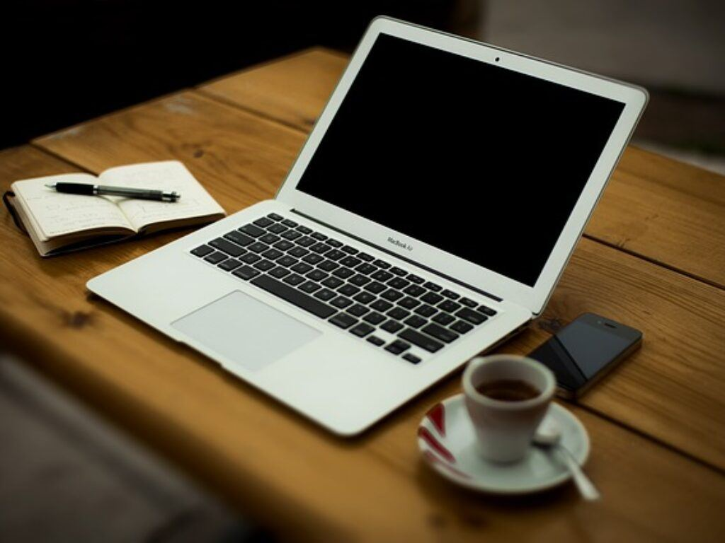 Photo of a laptop with a pen and paper tablet, cup of coffee and smartphone lying next to it on a wooden table