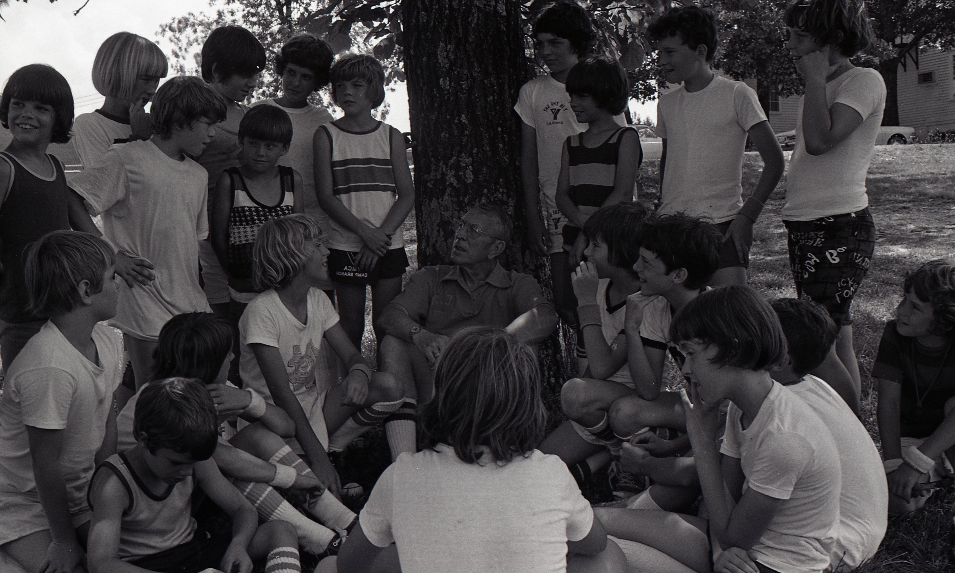 John Wooden sits under tree and is surrounded by basketball camp kids