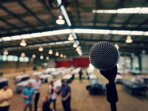 Microphone stand on stage in a barn with conference tables.