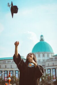 Woman in graduation gown smiling and tossing her graduate cap into the air.