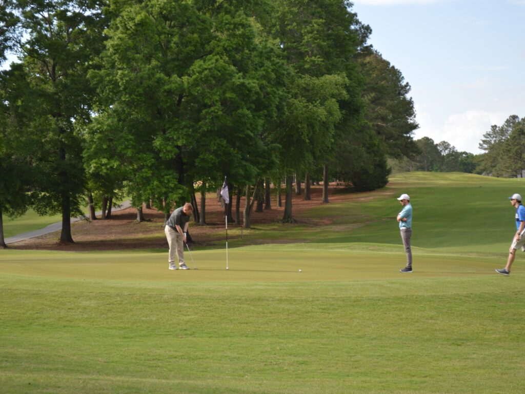 Two members of the harnett health team putting on the green at cphs golf tournament