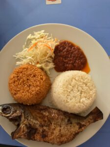 Photo of a whole fried fish on a white plate with two round piles of white and red rice and slaw and red sauce