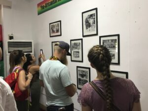 Photo of Campbell Law students looking at photos on a museum wall in Ghana