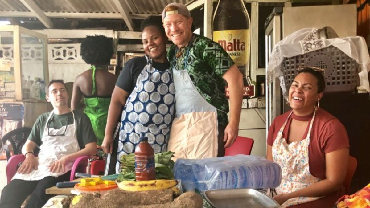 Photo of law student and Professor Shawn Fields hugging in front of table of food while in a cooking class in Ghana