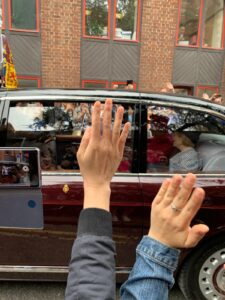 Photo of Queen Elizabeth inside a passing car with hands waving