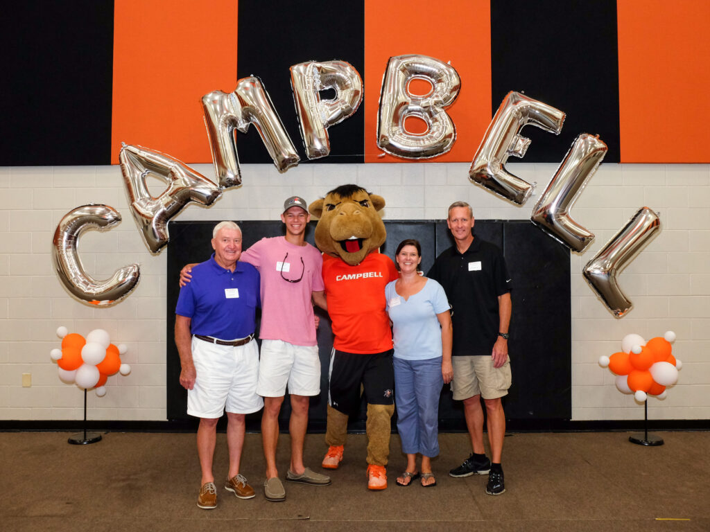 Rodgers Family standing in front of balloons that spell out CAMPBELL.