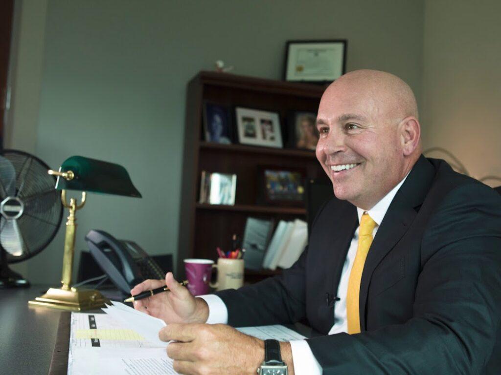 Photo of Hoyt Tessener sitting at desk smiling