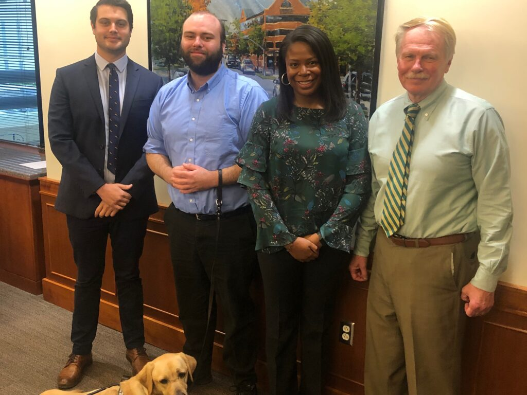 Photo of 2018-19 Wallace Fellows Brennan Cumalander, Cody Davis, his service dog Clark, and Morgan Pierce with Dean Leonard in Dean's Conference Room