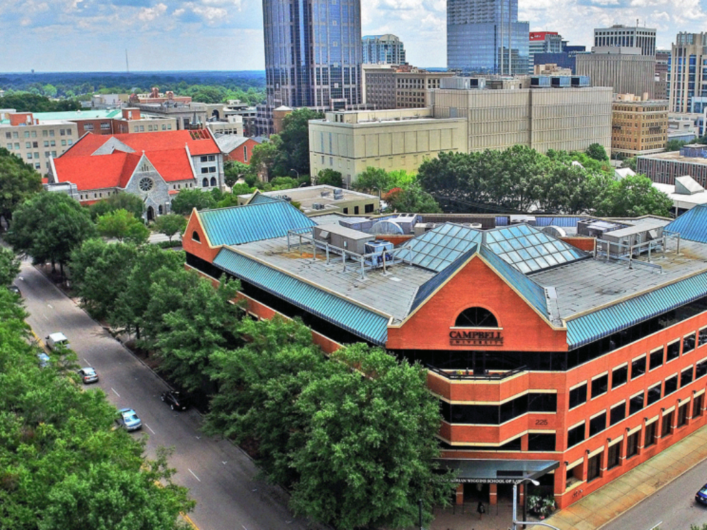 Photo of law school building exterior with Raleigh skyline in background