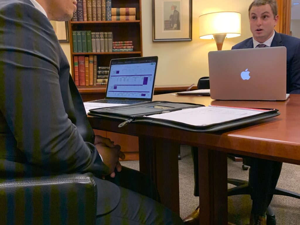 Photo of two male Campbell Law advocates sitting at a table in front of their Apple computers practicing.