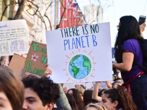 Photo of student protestors holding sign saying there is no planet B on a white background with drawing of blue globe