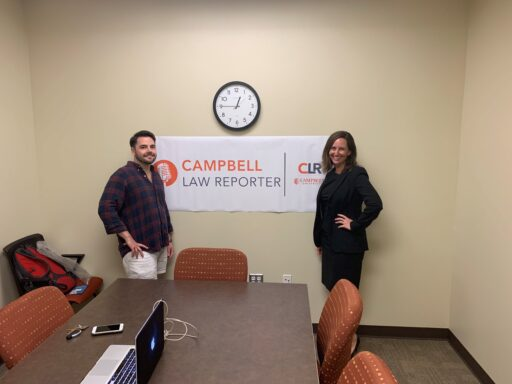 Photo of Bryant Pernell '20 and Professor Elizabeth Berenguer standing in frnot of the Campbell Law Reporter banner hanging in a confernce room under a wall clock