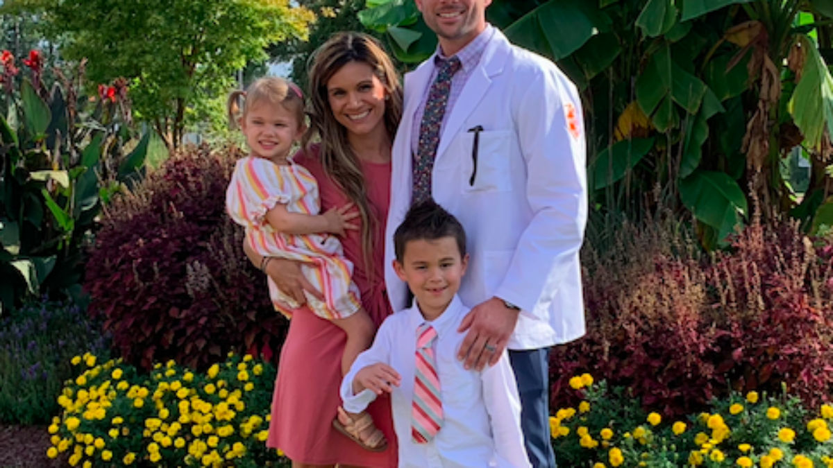 Sean Childress stands with wife and two kids