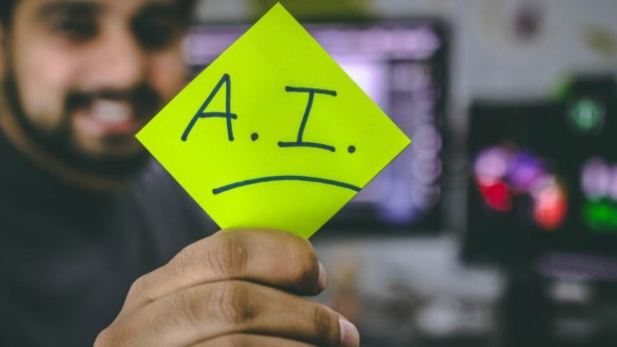 Photo of a man holding a yellow sticky note wit the letters A.I. written on it