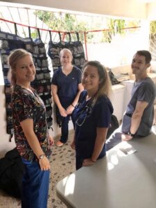 students on mission trip stop their work to smile for a photo