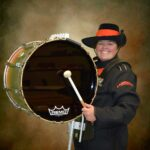 Olivia Exum Senior Drum Captain holding her Bass Drum in Marching Band Uniform